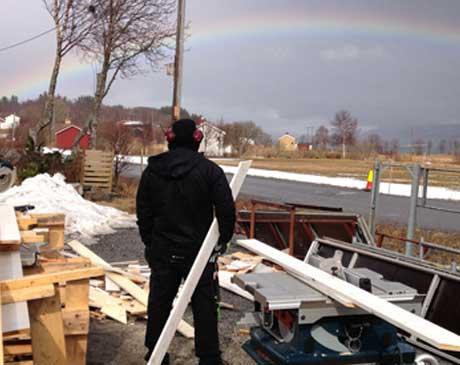 Bilde av ansatt som ser på regnbuen fra byggområde